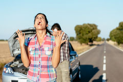 Desperate woman suffering car breakdown. Desperate women praying desperately because of car problems. Despair couple waiting for help after engine breakdown Royalty Free Stock Image
