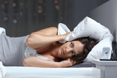 Desperate woman trying to sleep hearing neighbour noise royalty free stock photography