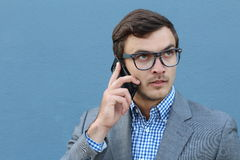 Desperate young brown-haired businessman get bad news heavy problems, faces challenges while talking on the mobile phone on blue Stock Images