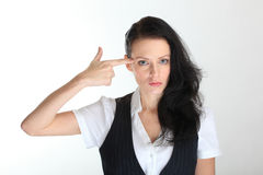 Desperate young business woman under pressure with a finger gun gesture Royalty Free Stock Images
