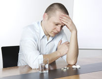 Desperate young Businessman with pills Royalty Free Stock Photos