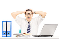 Desperate young businessman shouting in his office. Isolated on white background Stock Image