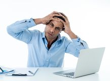 Desperate young businessman working on laptop going crazy with loads of work royalty free stock photo