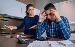 Desperate young couple with debts reviewing their Royalty Free Stock Image