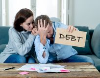 Desperate young Couple showing debt sign having financial problems feeling stressed paying bills royalty free stock images