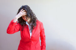 Desperate young girl. A young lady between 20 and 30 years old dressed in a coral jacket in a desperate situation royalty free stock photography