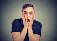 Desperate young man looking scared stock photos