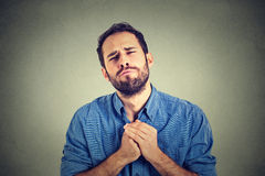 Desperate young man showing clasped hands, pretty please asking help forgiveness Stock Photography