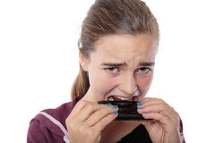 Desperate young woman bites in her smart phone Stock Photography