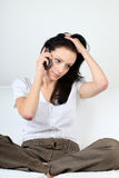 Desperate young woman communicates via her cell phone having her hand in hair Stock Images