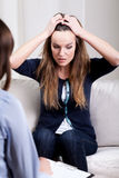 Desperate young woman on psychotherapy session Royalty Free Stock Images