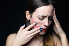 Desperate young woman touching her face. Concept of abuse and de Stock Photos