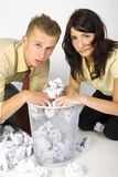 Desperation. Young desperate businessman nad businesswoman. Seraching something in garbage. Looking at camera. Gray background Royalty Free Stock Photography
