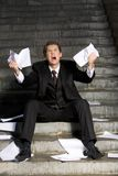 Desperation. Image of grieving businessman crying with papers in hands Stock Photo