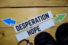 Desperation eller hopp mitt emot riktningstecken med glasögon och kängor på trä royaltyfri bild