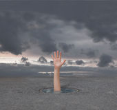 Desperation. Hand of drowning man in a small puddle of water Royalty Free Stock Images