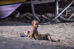 Desperation. A little, tiny boy, looking at the camera with pure desperation. Children of the fishing villages of Indonesia often suffer from starvation Royalty Free Stock Image