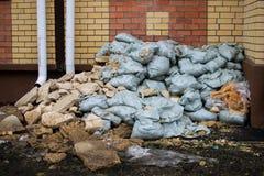 Desperdício da construção sob as janelas da casa na rua imagem de stock