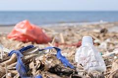 Desperdício e lixo do plástico em Sandy Beach Conceito do problema da poluição ambiental imagens de stock royalty free