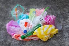 Desperdício plástico colorido, sacos, copos, garrafas, palhas no cimento foto de stock