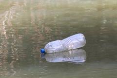 Desperdício plástico na superfície da água suja, água podre da garrafa, desperdício da garrafa imagens de stock