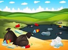 Desperdícios no rio e na terra Fotografia de Stock