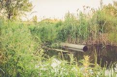 Desperdice o volume de água da tubulação de água no rio/conceito da ecologia: o esgoto derrama desperdiça para fora ao rio imagens de stock