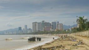 Desperdicios del frunce de la gente en la playa por la casa arruinada después del tifón