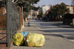 Desperdicios del hogar en mentiras de clasificación multicoloras de los bolsos en una calle de la ciudad cerca de la cerca del te imagenes de archivo