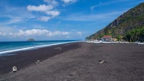 Desperdicios en la playa de la arena negra Fotos de archivo libres de regalías