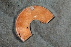 Desperdicios oxidados del metal en la arena negra fotos de archivo