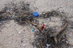 Desperdicios plásticos del biro de la pluma del top de la tapa azul roja de la botella en la playa blanca de México Yucatán Corel fotos de archivo