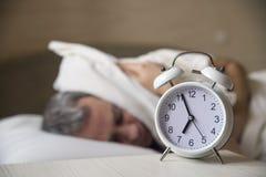 Despertado encima del hombre que miente en la cama que apaga un despertador por la mañana en 7am foto de archivo