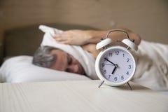 Despertado encima del hombre que miente en la cama que apaga un despertador por la mañana en 7am imagen de archivo