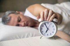 Despertado La mano apaga el despertador que despierta en la mañana imagen de archivo libre de regalías