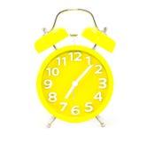 Despertador amarillo en blanco fotos de archivo
