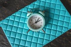 Despertador análogo azul do metal no fundo azul à moda Conceito do tempo em cores pasteis e escuras imagem de stock