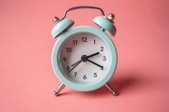 Despertador análogo azul do metal no fundo cor-de-rosa à moda Conceito do tempo nas cores pastel fotografia de stock