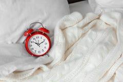 Despertador análogo e cobertura macia na cama foto de stock royalty free