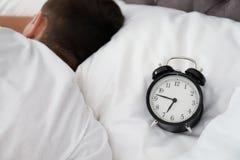 Despertador análogo e homem sonolento na cama fotos de stock royalty free