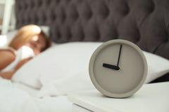 Despertador análogo e mulher sonolento borrada imagem de stock royalty free
