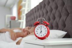 Despertador análogo e mulher sonolento borrada foto de stock