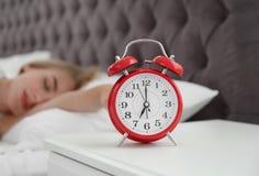 Despertador análogo e mulher sonolento borrada fotos de stock