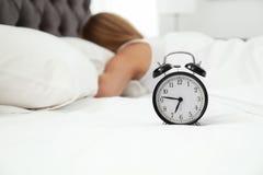 Despertador análogo e mulher sonolento na cama imagens de stock royalty free