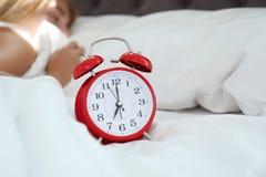 Despertador análogo e mulher sonolento na cama foto de stock