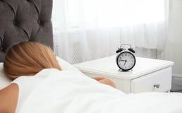 Despertador análogo e mulher sonolento no quarto imagens de stock