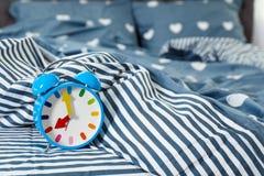 Despertador análogo na cama fotografia de stock royalty free
