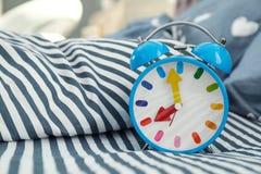 Despertador análogo na cama imagens de stock