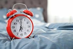 Despertador análogo na cama foto de stock