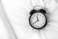 Despertador análogo na cama, vista superior imagens de stock
